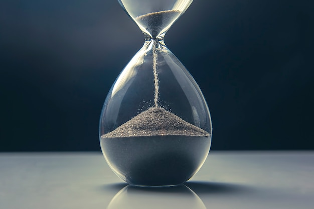 Hourglass on a light wall. time is money. business solutions in time.