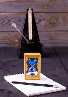 Песочные часы, метроном и блокнот с карандашом