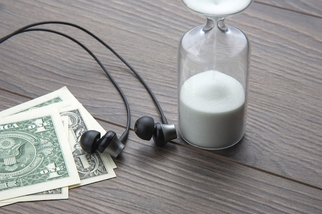 砂時計、お金、ヘッドフォンがテーブルにあります