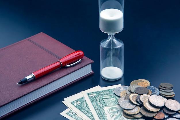 砂時計、お金、ペン、ノートがテーブルにあります