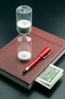 На столе лежат песочные часы, деньги, ручка и блокнот