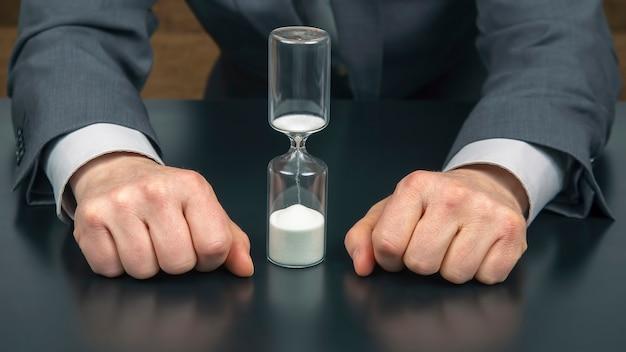 사업가의 손 옆에 모래 시계. 업무 시간. 성공 목표 계획