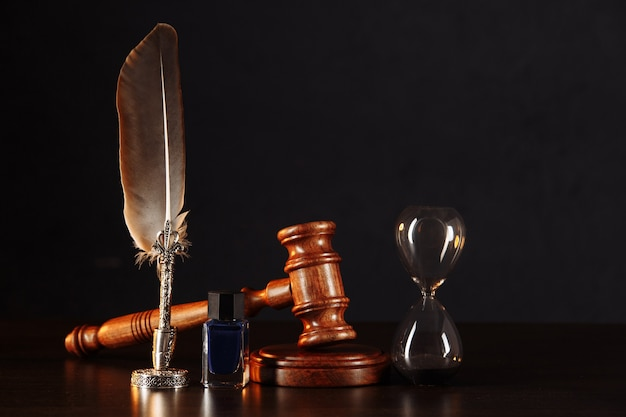 Hourglass, notary's public pen, and stamp on testament and last will on the wooden table.