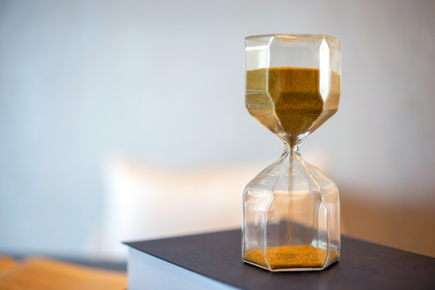 Hourglass and old book with blurred background. leave copy space for adding text.