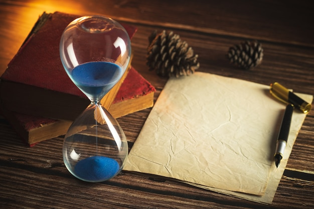 Hourglass and old books with old paper and pen on wooden tables in lighting of the lantern.