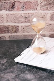 Песочные часы на календаре и текущие через лампочку песочных часов