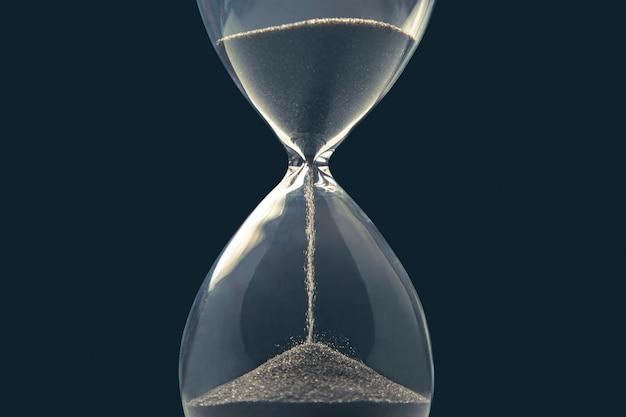 어두운 배경에 모래 시계입니다. 시간은 돈이다. 적시에 비즈니스 솔루션.