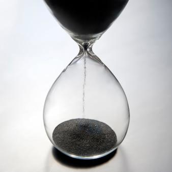 Песочные часы на светлой поверхности. время - деньги