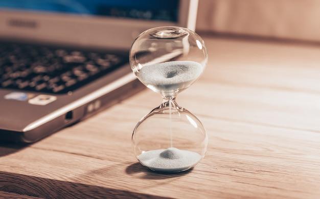Песочные часы на светлом деревянном столе с ноутбуком или компьютером. время ускользает из моих пальцев.