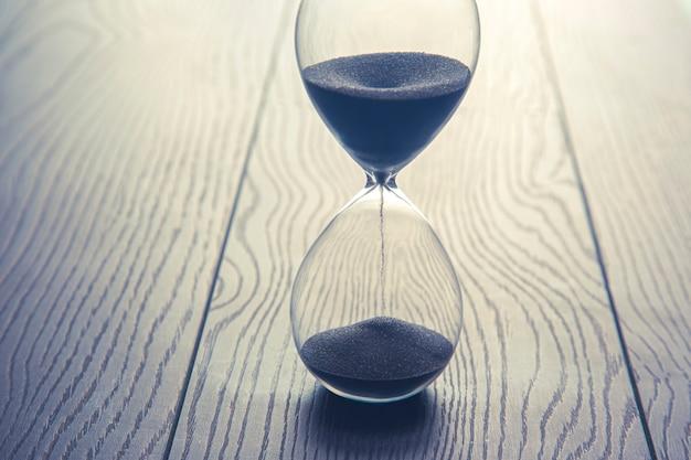 나무 테이블에 모래 시계입니다. 시간은 돈이다. 적시에 비즈니스 솔루션.
