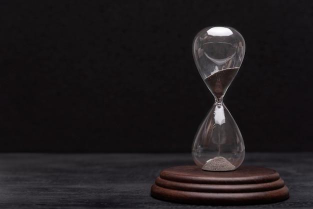 Песочные часы на черном фоне. актуальность и исход времени. тайм-менеджмент.