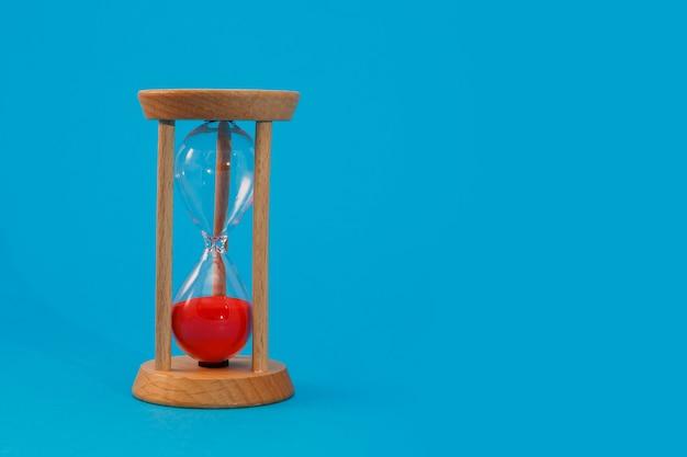 Песочные часы на синем изолированном