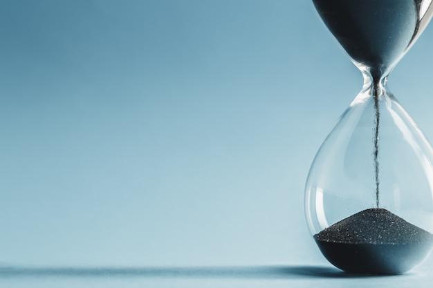 Песочные часы на синей поверхности