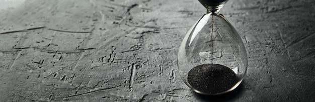 어두운 배경, 긴 배너에 모래 시계. 긴급 및 시간 부족 개념