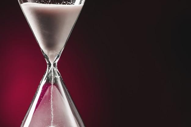 Песочные часы на темном цвете. концепция управления временем