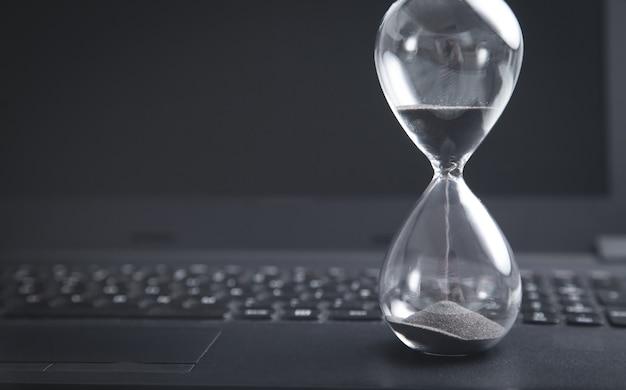 ノートパソコンのキーボードの砂時計。時間。ビジネス