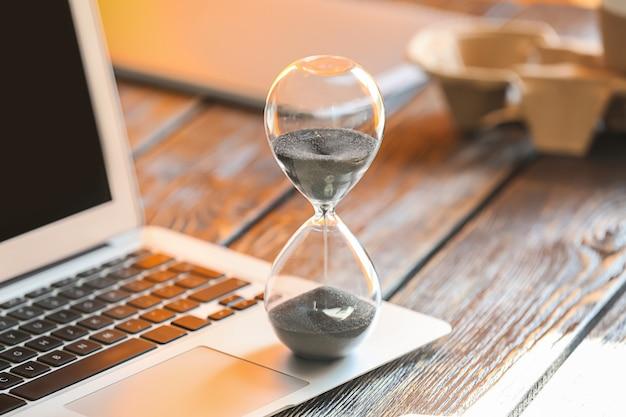 Песочные часы на клавиатуре ноутбука. концепция управления временем