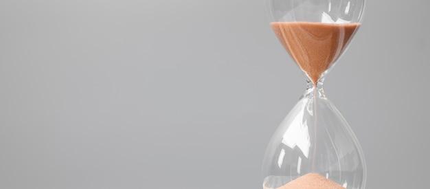 Песочные часы на столе в офисе с копией пространства, песок течет через лампочку песочных часов, измеряя время прохождения. обратный отсчет, крайний срок, время жизни и пенсионное понятие