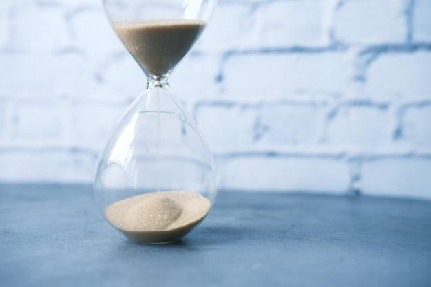 Песочные часы на столе, песок течет через лампочку песочных часов.