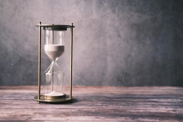 Песочные часы на столовом песке, протекающем через луковицу песочных часов