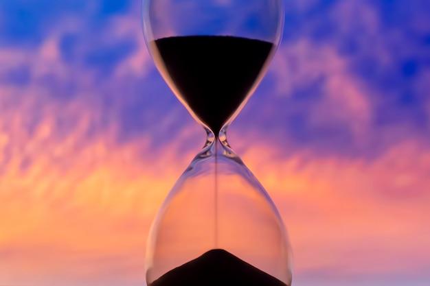 Песочные часы на фоне закатного неба. ценность времени в жизни. вечность.
