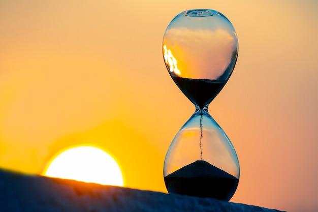일몰의 배경에 모래 시계입니다. 인생에서 시간의 가치. 영원.