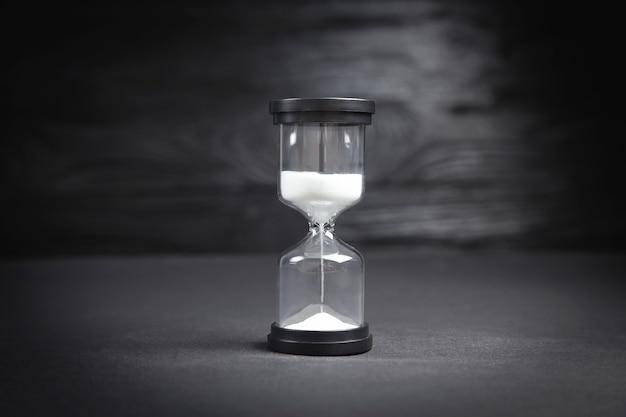 Песочные часы на черном фоне.