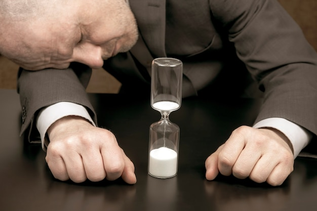 피곤하고 우울한 사업가의 모래 시계. 작업 시간 분배. 결정을 내릴 시간입니다. 늦은 사업 기회