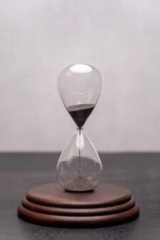 Песочные часы на подставке. актуальность и исход времени. тайм-менеджмент. вертикальная рамка.