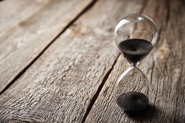 木製の背景に砂時計、クローズアップ。緊急性と時間切れの概念