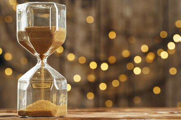 흐린 된 빛 배경 나무 책상에 모래 시계
