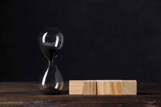 큐브 나무 블록 근처 모래 시계 또는 모래 시계, 텍스트, 어두운 나무 테이블에 장소.