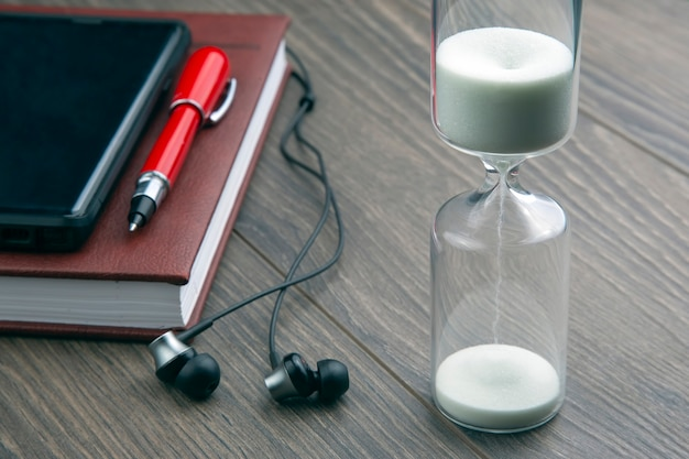 모래 시계, 펜, 노트, 이어폰이 테이블 위에 있습니다. 비즈니스 사무실 항목. 시간은 돈이다. 적시에 비즈니스 솔루션.