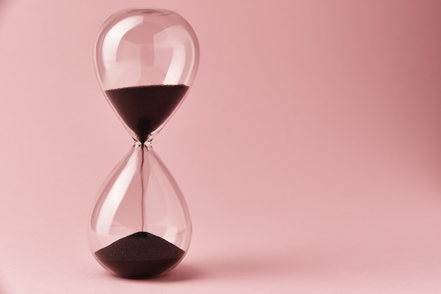 Hourglass on pink background, close up. urgency and running out of time concept