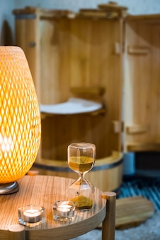 砂時計。規制、手順の時間管理。ミニフィトサウナ-杉樽。スパトリートメント。木風呂。健康の概念、あなたの体の世話をします。