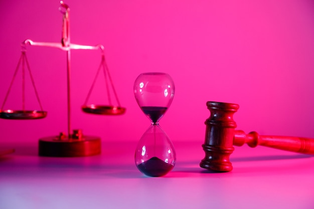 Песочные часы, весы и деревянный судейский молоток розового неона.