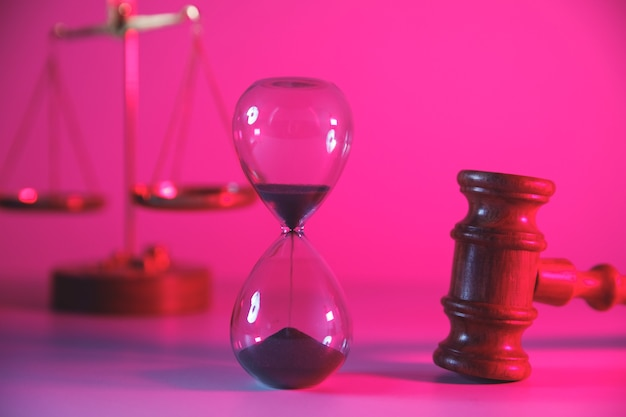 Hourglass, scales and wooden judge gavel.