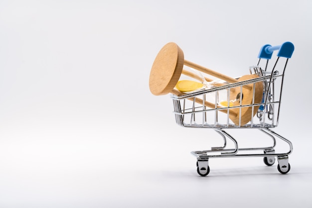 Hourglass in shopping cart on white
