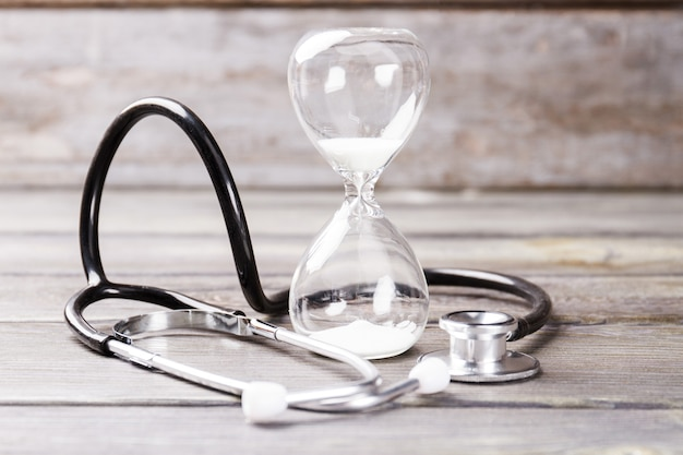 Hourglass and stethoscope. short living concept.