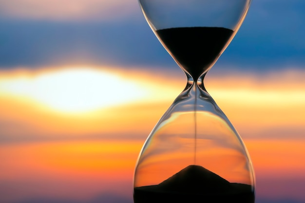 Hourglass over a sunset. the value of time in life. an eternity.