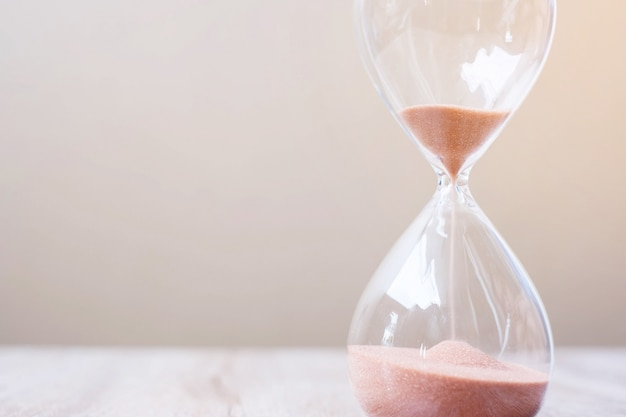 Hourglass on table, sand flowing through the bulb of sandglass measuring the passing time. countdown, deadline, life time and retirement concept
