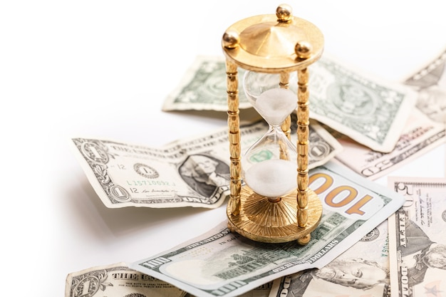 Hourglass and us dollar banknotes. concept of investment or inflation.