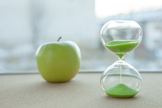 Hourglass with an apple in the background, close-up