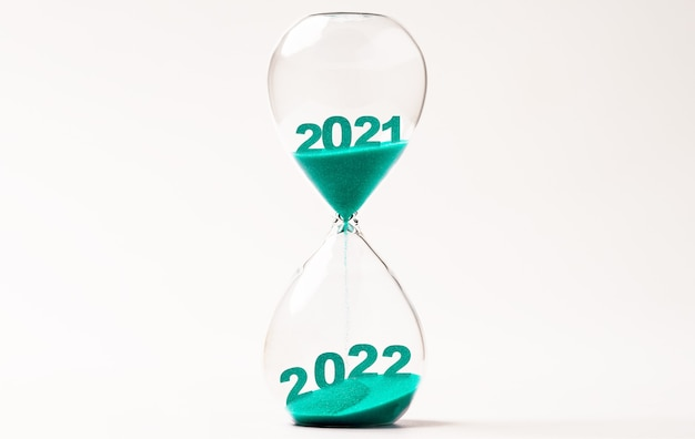 Hourglass with blue sand for change 2021 to 2022 year , countdown and preparation merry christmas and happy new year concept.