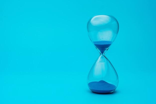 Песочные часы с голубым песком на синем фоне