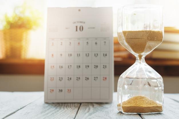 나무 책상에 달력으로 모래 시계를 닫습니다. 시간 개념