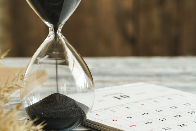 Hourglass with calendar on wooden desk close up