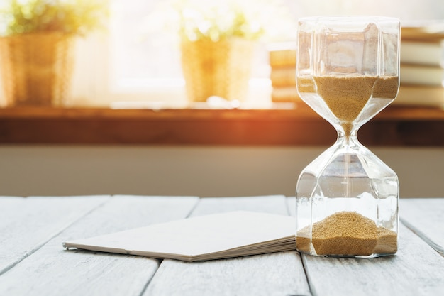 Hourglass with calendar on wooden desk