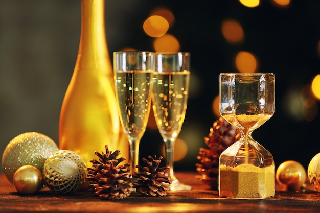 Hourglass with christmas decor and champagne on table against defocused lights