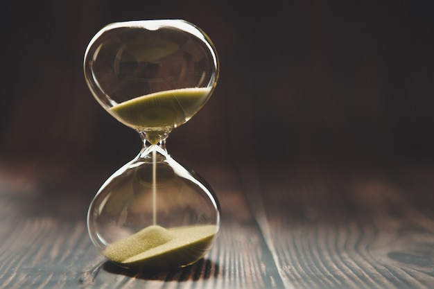 Hourglass with falling sand inside a glass bulb, passing time or lost time